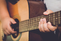Finger of boy play guitar in vintage image tone. Royalty Free Stock Image