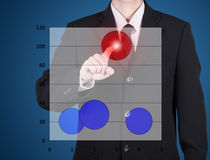 Finger of business man press to red circle chart. On blue blackground Royalty Free Stock Image