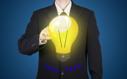 Finger of businessman press to bulb with new idea reflect paint. On suit, blue background Stock Photography