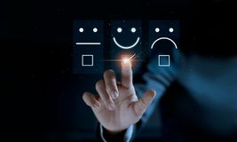 Finger of businessman touching and check mark icon face emoticon smile on dark background. Service mind, service rating. Satisfaction and customer service stock photo