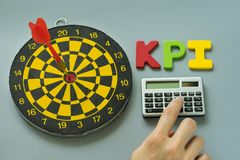 Finger on calculator and colorful alphabet KPI with dartboard as Royalty Free Stock Images
