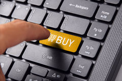 Finger clicks BUY keyboard button. A finger gesturing about to click the BUY button on a computer keyboard Royalty Free Stock Photos