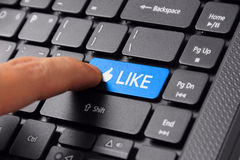 Finger clicks LIKE button. Closeup of a finger clicking the LIKE button on a computer keyboard royalty free stock photo