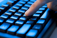 Finger Computer Keyboard. A finger pressing down on a computer keyboard Royalty Free Stock Image