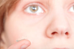 Finger with contact lens in front of female face Royalty Free Stock Photos