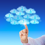 Finger Contacting Workforce Via Cloud. Index finger of a white collar worker is touching a cloud icon to connect with many peers in cyberspace. Numerous cloud Stock Image