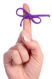 A finger contains a bow-tied string as a reminder Stock Photography