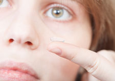 Finger with corrective lens and female face Stock Images