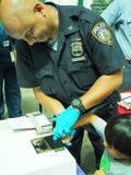 Finger de la policía de NYC que imprime a un niño para el programa de tarjeta seguro Fotos de archivo libres de regalías