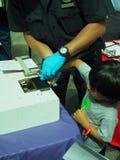 Finger de la policía de NYC que imprime a un niño para el programa de tarjeta seguro Foto de archivo