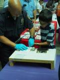 Finger de la policía de NYC que imprime a un niño para el programa de tarjeta seguro Imágenes de archivo libres de regalías