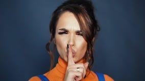 Finger de la tenencia del silencio de la muestra de la demostración de la mujer cerca de los labios Cabeza de sacudida morena bon almacen de video