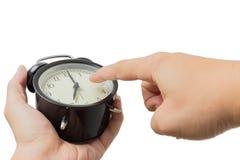 Finger del punto de la mano del primer en el reloj aislado en blanco Foto de archivo