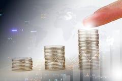 Finger, der auf den höchsten Münzenstapel auf unscharfer Stadt, Weltkarte und Diagramm zeigt Lizenzfreie Stockfotografie