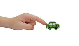 Finger, der auf ein hölzernes Auto drückt Lizenzfreies Stockbild
