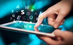 Finger, der auf Tabletten-PC, Buchstabekonzept zeigt Stockbild