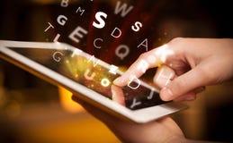 Finger, der auf Tabletten-PC, Buchstabekonzept zeigt Stockfotografie