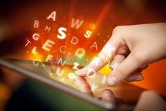 Finger, der auf Tabletten-PC, Buchstabekonzept zeigt Stockbilder