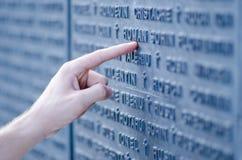 Finger, der Buchstaben einer Erinnerungswand zeigt Stockbilder