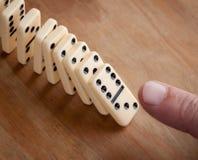Finger, der Dominostücke drückt Lizenzfreie Stockfotos
