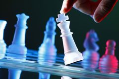 Finger, der eine Schachfigur auf Schach-Brett kippt Stockbild
