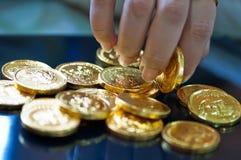 Finger der Frau, die Goldmünzen anhalten Stockbild