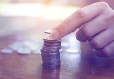 Finger der Frau Silbermünze stapelnd, um für die Rettung anzuhäufen, weiblich Lizenzfreie Stockbilder