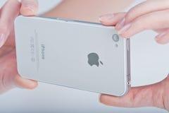 Finger der Frauen hält weißes iphone 4 Lizenzfreies Stockbild