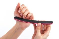 Finger des Frauenpoliernagels an Hand mit Nagelfeile auf weißem Hintergrund Stockbilder