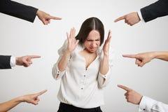 Finger, die auf betonte Geschäftsfrau zeigen Stockfotografie