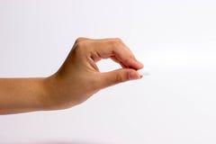 Finger, die eine Pille halten Lizenzfreie Stockbilder