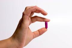 Finger, die eine Pille halten Lizenzfreies Stockbild