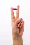 Finger, die eine Pille in v-Zeichen halten Stockbild