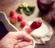 Finger dipped in strawberry jam. Homemade strawberry jam (marmelade) Stock Photography