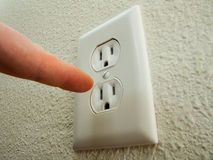Finger doesn't go there. Trying to touch the outlet this man can get zapped Royalty Free Stock Photos