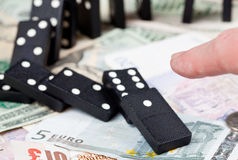 Finger on dominoes on bank notes Royalty Free Stock Image