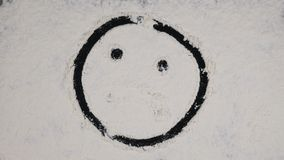 Finger drawing funny smiley on a white flour background. top view 4k.  stock footage