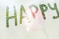 A finger drawing of the shape of the stripe of the word happy on a semitransparent misted glass. raindrops of spring rain on the. Window close-up. blurred royalty free stock images