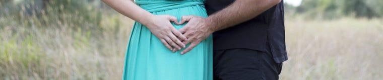 Finger eines Paares, das Herz bildet, formen auf Frauenbauch Stockfotografie