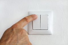 Finger at electric light switch Stock Photos