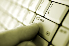 Finger on enter key. A finger pressing the enter key stock image