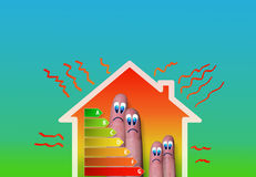 House with a bad energy classification. Finger family house with bad energy classification on green background Stock Photos