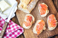 Finger food. Appetizer canapes sandwiches with baguette, salmon and butter on rustic wooden board over wood background. Top view,. Copy space, horizontal Stock Images
