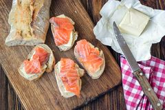 Finger food. Appetizer canapes sandwiches with baguette, salmon and butter on rustic wooden board over wood background. Top view,. Copy space, horizontal Stock Image
