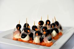 Finger food, funny edible little penguins. Edible small penguins made from black olives cheese carrots and a  scarf made from ham, hearty in the taste Stock Photo