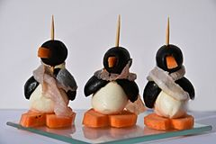 Finger food, funny  edible small penguins. Edible small penguins made from black olives cheese carrots and a  scarf made from ham, hearty in the taste Stock Image