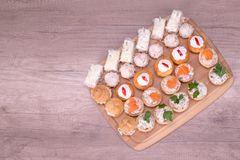 Finger food, top view. Nice decorated catering on a wooden plate Stock Image