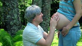 Finger futuro de la demostración del padre para arriba que mira la cámara y que frota ligeramente el vientre embarazada de la esp almacen de video