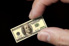 Finger halten eine kleine Dollaranmerkung an Lizenzfreie Stockfotos