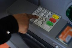 Person pressing pin code on ATM bank machine. Finger of hand pressing number buttons on keypad of ATM showing the concept of bank transaction royalty free stock images
